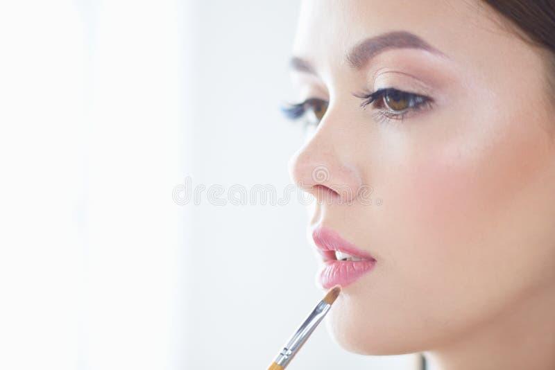 Το όμορφο κορίτσι με την καλλυντική βούρτσα σκονών για αποτελεί makeup Σύνθεση που ισχύει για το τέλειο δέρμα στοκ εικόνα