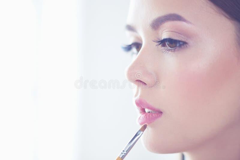 Το όμορφο κορίτσι με την καλλυντική βούρτσα σκονών για αποτελεί makeup Σύνθεση που ισχύει για το τέλειο δέρμα στοκ εικόνα με δικαίωμα ελεύθερης χρήσης