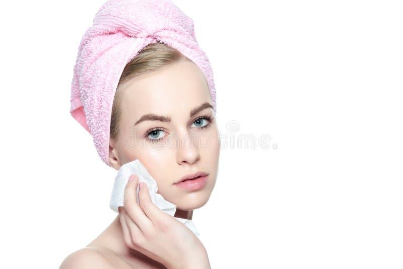 Το όμορφο κορίτσι με την τέλεια χροιά που καθαρίζει το πρόσωπό της που χρησιμοποιεί το μαλακό πρόσωπο σκουπίζει Απομονωμένος στην στοκ φωτογραφίες με δικαίωμα ελεύθερης χρήσης