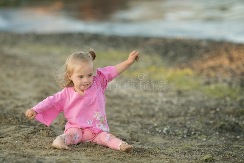 Το όμορφο κορίτσι με το κάτω σύνδρομο επιδεικνύει πώς ένα πουλί πετά στην παραλία στοκ φωτογραφία με δικαίωμα ελεύθερης χρήσης