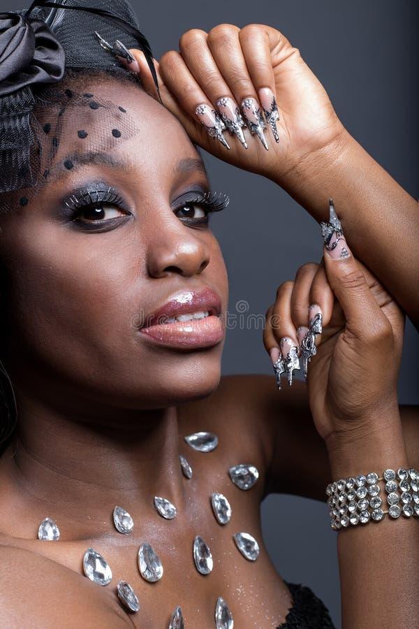Το όμορφο κορίτσι με το σκοτεινό δέρμα και τα μακριά ακρυλικά καρφιά στο Μαύρο ντύνουν στο στούντιο στοκ εικόνα με δικαίωμα ελεύθερης χρήσης