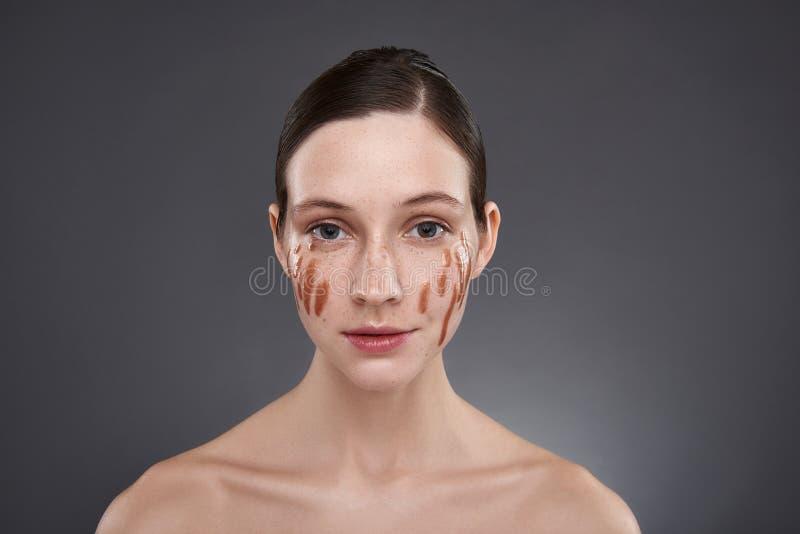 Το όμορφο κορίτσι με το χρυσό χείλι σχολιάζει στα μάγουλα που στέκονται στο γκρίζο κλίμα στοκ φωτογραφίες με δικαίωμα ελεύθερης χρήσης