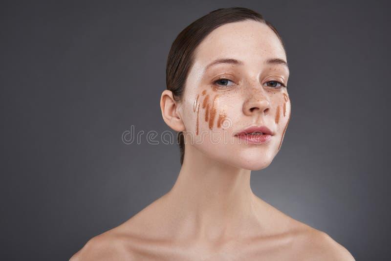 Το όμορφο κορίτσι με το χρυσό χείλι σχολιάζει στο πρόσωπό της την τοποθέτηση στο γκρίζο κλίμα στοκ εικόνες με δικαίωμα ελεύθερης χρήσης