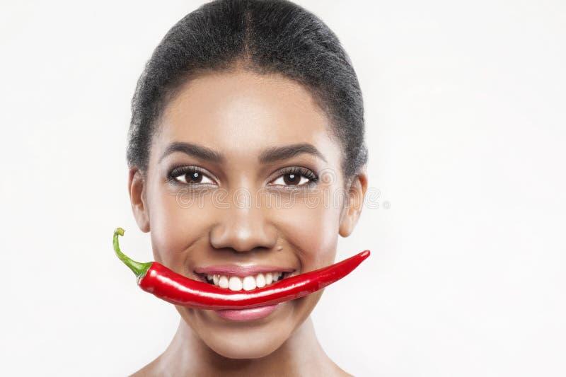Το όμορφο κορίτσι μιγάδων τρώει το πικάντικο πιπέρι στοκ φωτογραφία με δικαίωμα ελεύθερης χρήσης