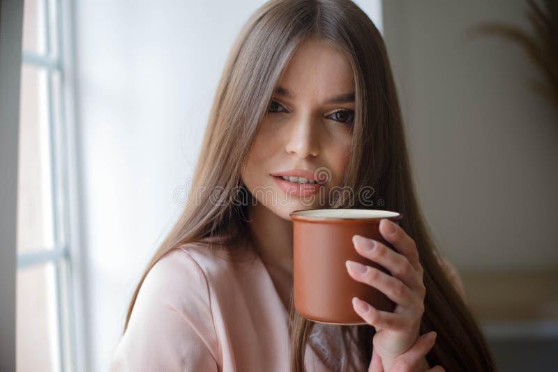 Το όμορφο κορίτσι πίνει τον καφέ και χαμογελά καθμένος στον καφέ στοκ φωτογραφία