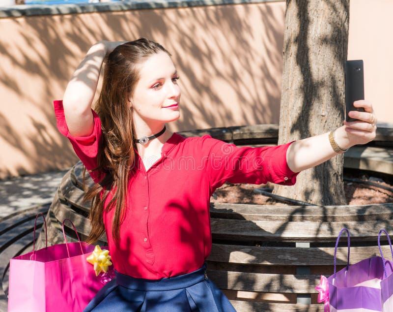 Το όμορφο κορίτσι παίρνει ένα selfie σε ένα smarphone στοκ φωτογραφία με δικαίωμα ελεύθερης χρήσης