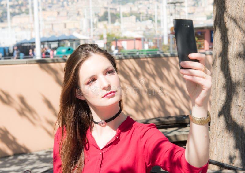 Το όμορφο κορίτσι παίρνει ένα selfie σε ένα smarphone στοκ εικόνα με δικαίωμα ελεύθερης χρήσης