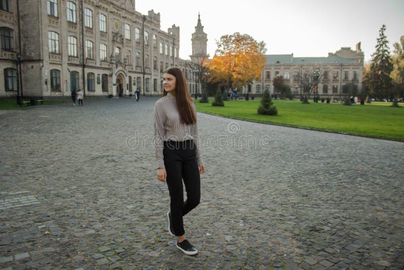Το όμορφο κορίτσι περπατά κοντά στη πανεπιστημιούπολη στοκ φωτογραφίες με δικαίωμα ελεύθερης χρήσης