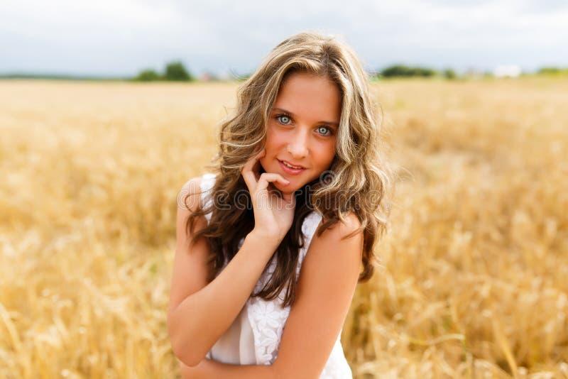 το όμορφο κορίτσι πεδίων φαίνεται χαμόγελα επάνω στις νεολαίες σίτου στοκ εικόνα