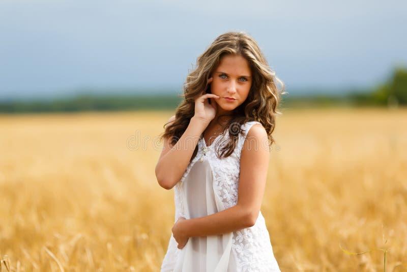το όμορφο κορίτσι πεδίων φαίνεται χαμόγελα επάνω στις νεολαίες σίτου στοκ φωτογραφίες