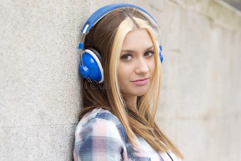 Το όμορφο κορίτσι πορτρέτου κινηματογραφήσεων σε πρώτο πλάνο ακούει μουσική με τα ακουστικά στοκ φωτογραφία