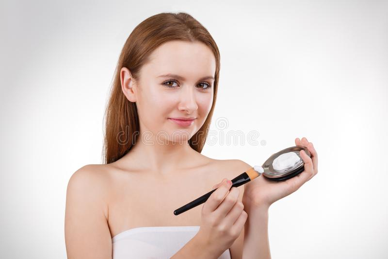 Το όμορφο κορίτσι που βάζει την του προσώπου κρέμα ή η μάσκα στο νέο πρόσωπο ξεφλουδίζει με τη βούρτσα από το βάζο στοκ φωτογραφία με δικαίωμα ελεύθερης χρήσης