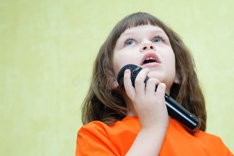 Το όμορφο κορίτσι που κρατά ένα μικρόφωνο τραγουδά και φαίνεται ανοδικό στοκ εικόνες με δικαίωμα ελεύθερης χρήσης