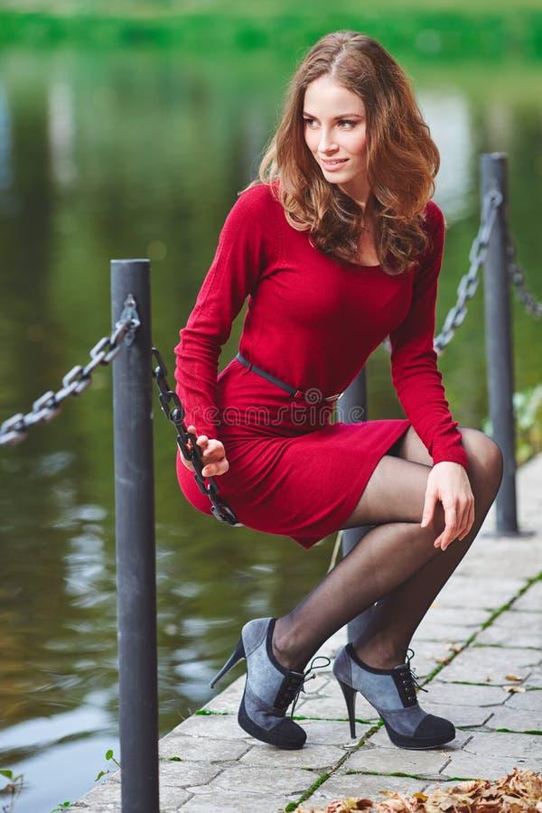 Το όμορφο κορίτσι σε ένα κόκκινο φόρεμα είναι κάθεται Υπαίθριο πορτρέτο στοκ φωτογραφίες