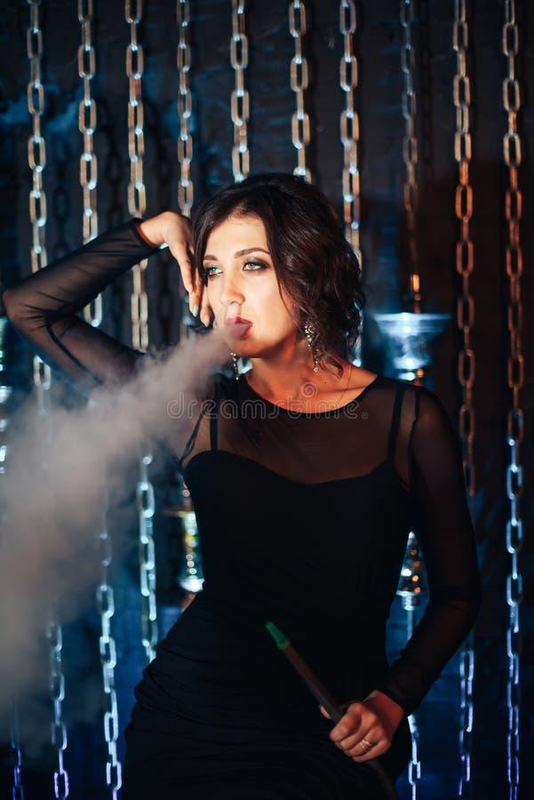 Το όμορφο κορίτσι σε ένα μαύρο φόρεμα καπνίζει hookah στις αλυσίδες υποβάθρου στοκ εικόνες με δικαίωμα ελεύθερης χρήσης