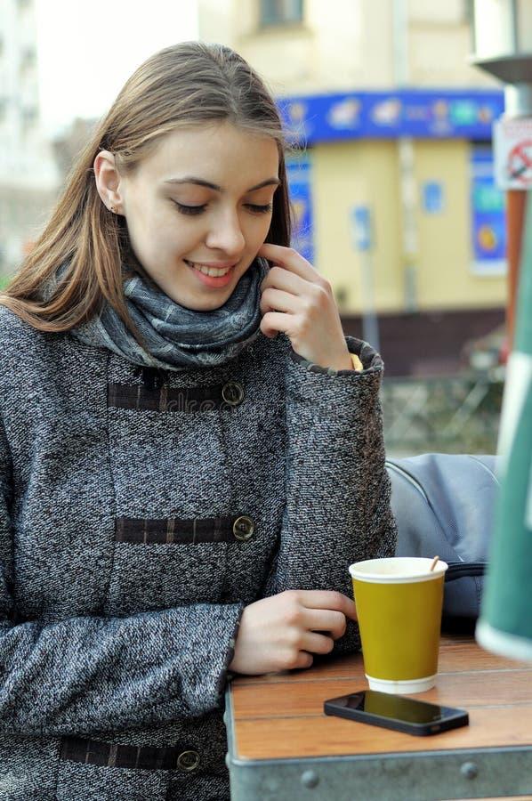 Το όμορφο κορίτσι σκέφτεται την κατανάλωση του καφέ ή την παραγωγή ενός τηλεφωνήματος στοκ εικόνες