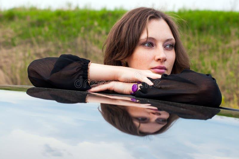 Το όμορφο κορίτσι στέκεται κοντά στο αυτοκίνητό της στοκ εικόνες