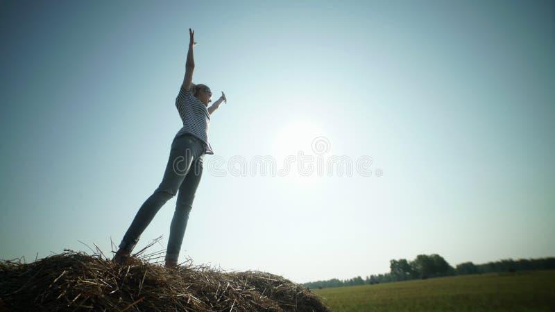 Το όμορφο κορίτσι στέκεται στις θυμωνιές χόρτου και τραβά τα χέρια στον ουρανό στοκ εικόνες