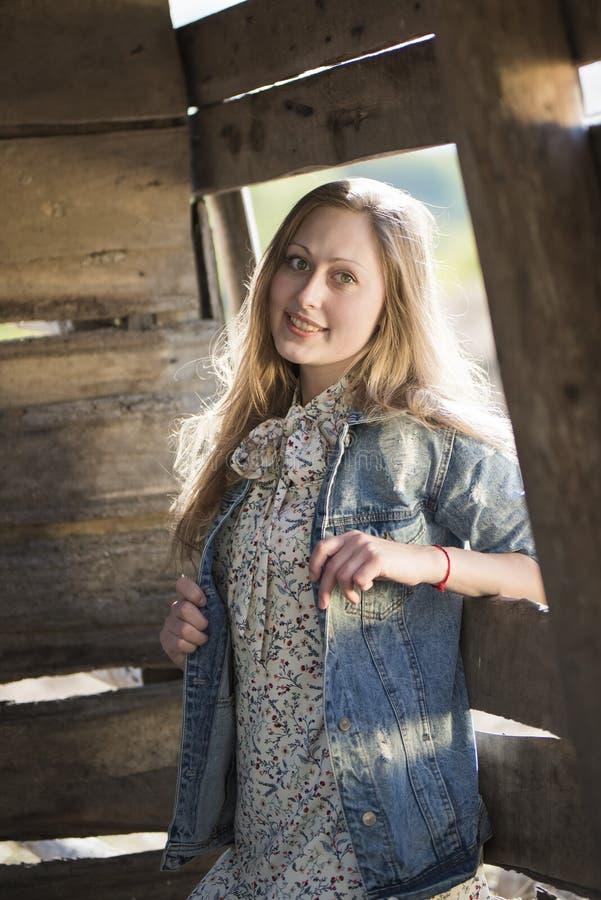 Το όμορφο κορίτσι στέκεται στο υπόβαθρο ενός παλαιών ξύλινων τοίχου και ενός παραθύρου στοκ εικόνες