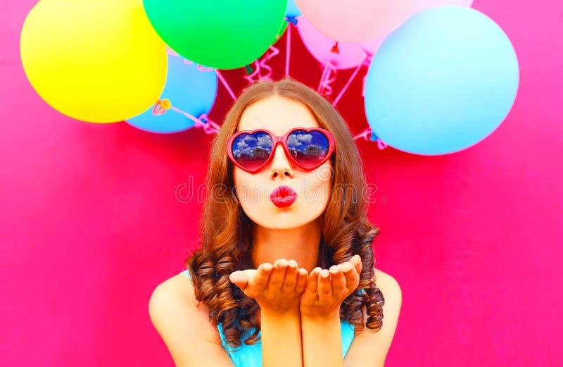 Το όμορφο κορίτσι στέλνει ένα φιλί αέρα κρατά έναν αέρα ζωηρόχρωμα μπαλόνια στοκ εικόνα