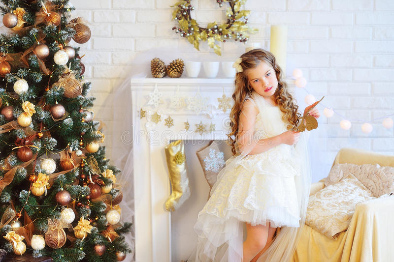 Το όμορφο κορίτσι στα Χριστούγεννα διακόσμησε το εσωτερικό στοκ φωτογραφίες