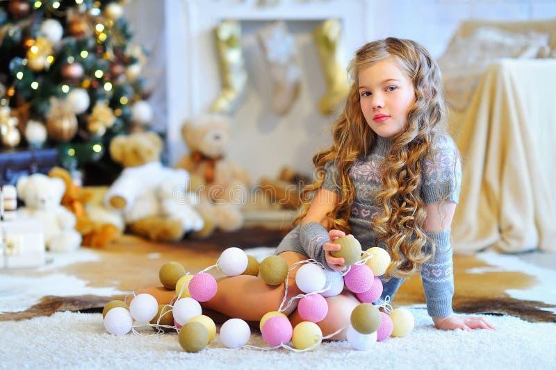 Το όμορφο κορίτσι στα Χριστούγεννα διακόσμησε το εσωτερικό στοκ εικόνες
