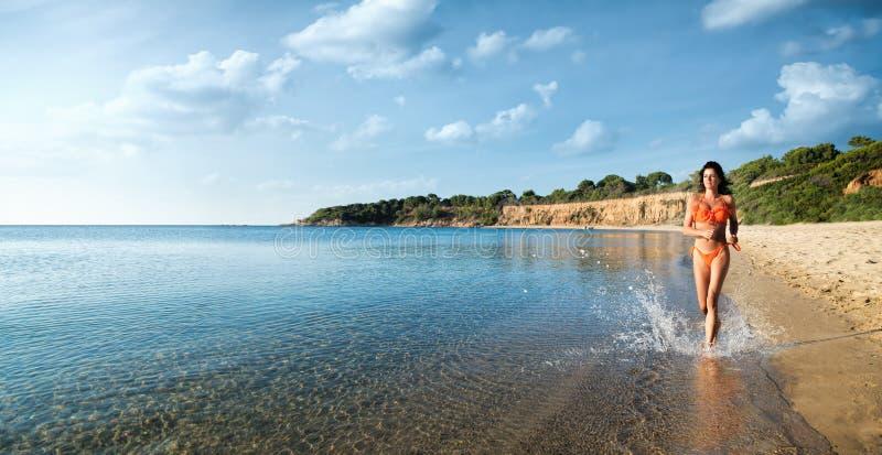 Το όμορφο κορίτσι στο μπικίνι τρέχει στην παραλία στοκ φωτογραφίες με δικαίωμα ελεύθερης χρήσης