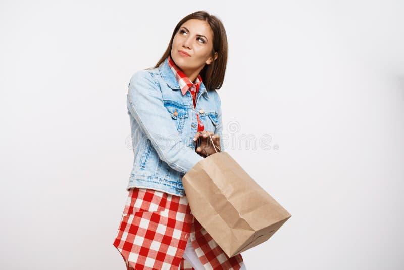Το όμορφο κορίτσι τη μοντέρνη άνοιξη φαίνεται τσάντα καφετιού εγγράφου εκμετάλλευσης στοκ εικόνες