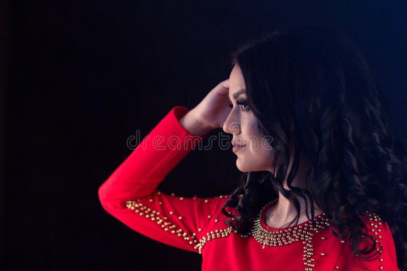 Το όμορφο κορίτσι brunette με μακρυμάλλη σε ένα κόκκινο φόρεμα ρυθμίζει την τρίχα της σε ένα μαύρο υπόβαθρο στενό απομονωμένο λευ στοκ φωτογραφία με δικαίωμα ελεύθερης χρήσης