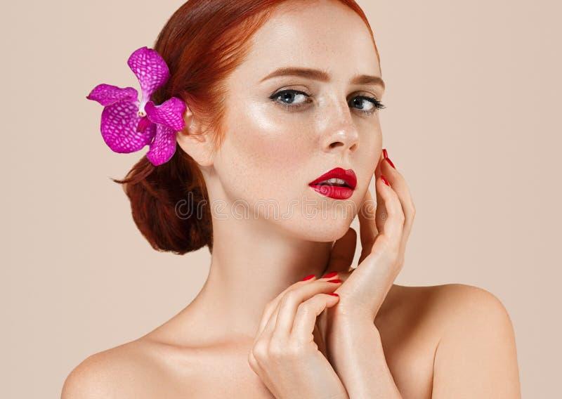 Το όμορφο κόκκινο πορτρέτο γυναικών τρίχας με το λουλούδι στην τρίχα τέλεια αποτελεί το μανικιούρ στοκ φωτογραφίες