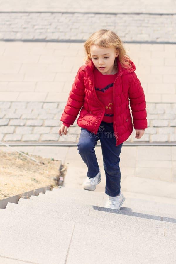 Το όμορφο μικρό κορίτσι αναρριχείται στα βήματα στοκ εικόνες