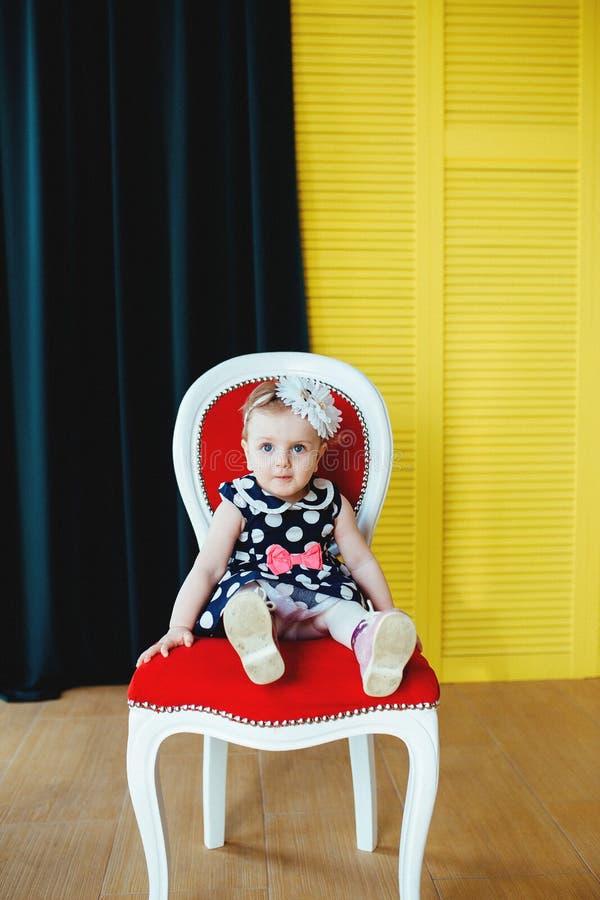 Το όμορφο μικρό κορίτσι κάθεται σε μια καρέκλα στοκ φωτογραφία