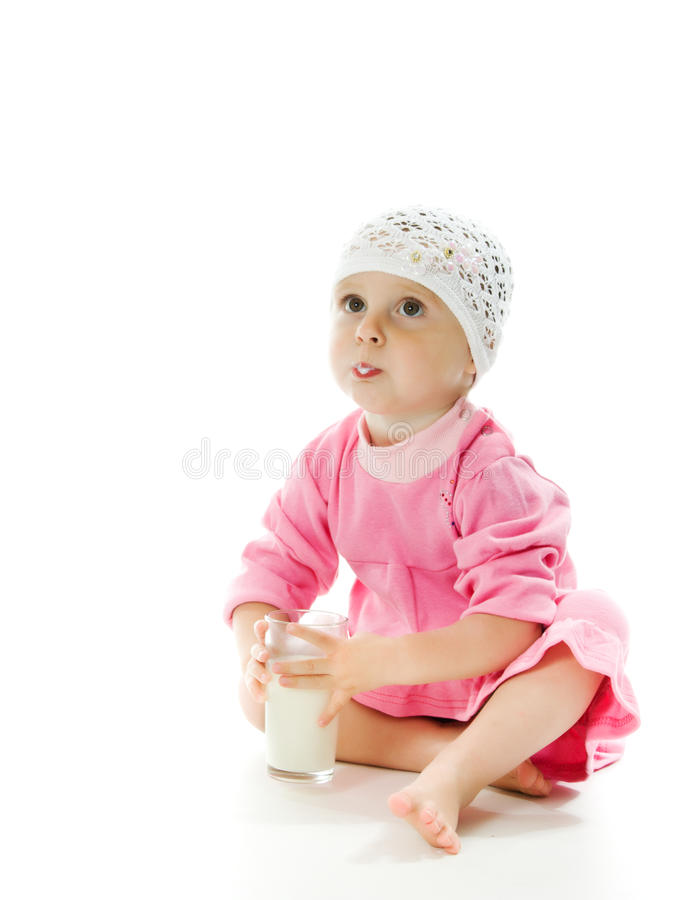 Το όμορφο μικρό κορίτσι κρατά ένα ποτήρι του γάλακτος στοκ φωτογραφία