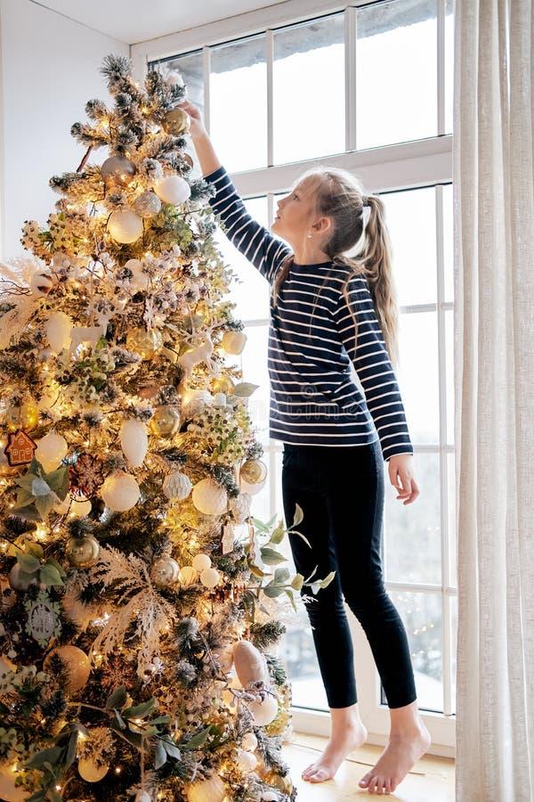Το όμορφο μικρό κορίτσι που ντύνεται στις πυτζάμες τοποθετεί ένα αστέρι πάνω από τα χριστουγεννιάτικα δέντρα στοκ εικόνα