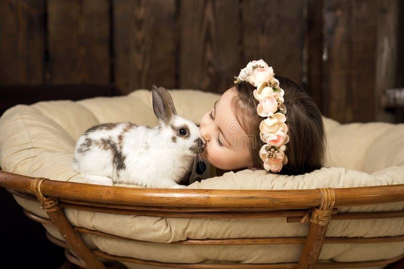 Το όμορφο μικρό κορίτσι σε ένα στεφάνι των λουλουδιών φιλά ένα χαριτωμένο χνουδωτό άσπρο λαγουδάκι Πάσχας στοκ εικόνα