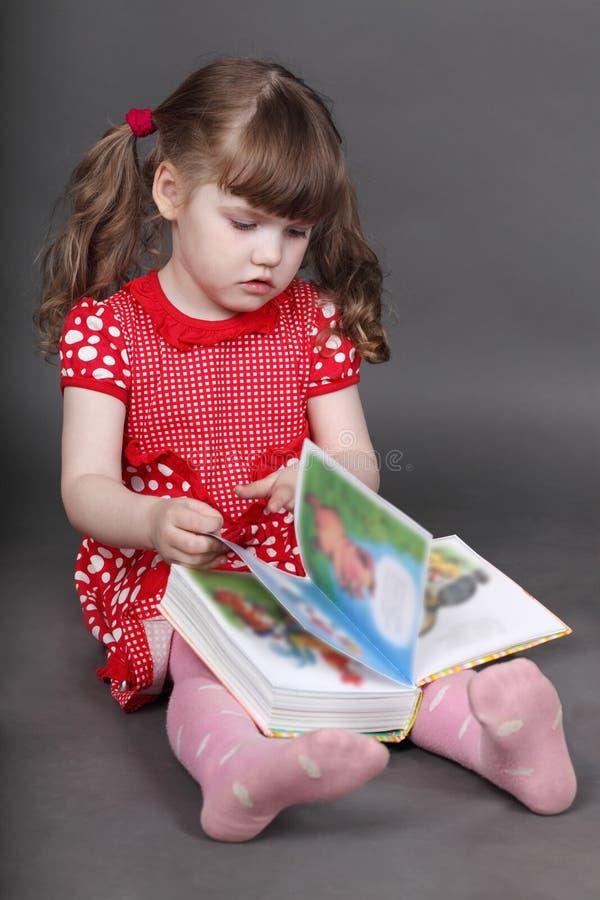 Το όμορφο μικρό κορίτσι στο κόκκινο φόρεμα κάθεται στο πάτωμα στοκ φωτογραφία