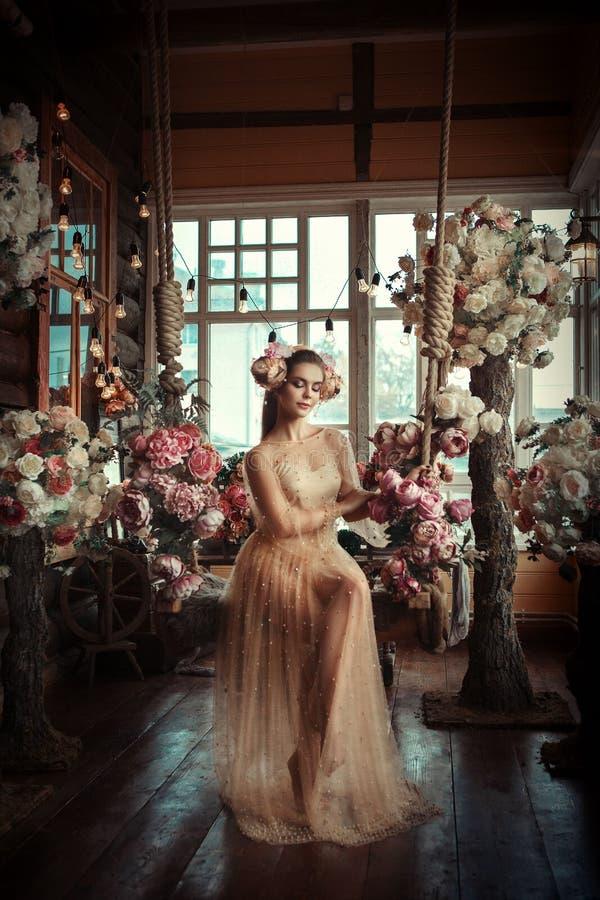 Το όμορφο μοντέλο ποζάρει με δημιουργικό μακιγιάζ και λουλούδια στοκ φωτογραφία