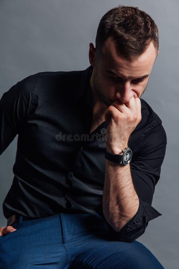 Το όμορφο μοντέρνο άτομο πορτρέτου σε ένα μαύρο πουκάμισο κάθεται σε μια καρέκλα σε μια σοφίτα στούντιο φωτογραφιών στοκ εικόνα με δικαίωμα ελεύθερης χρήσης