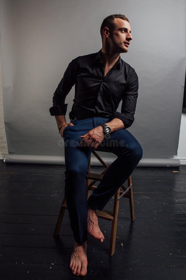 Το όμορφο μοντέρνο άτομο πορτρέτου σε ένα μαύρο πουκάμισο κάθεται σε μια καρέκλα σε μια σοφίτα στούντιο φωτογραφιών στοκ φωτογραφία με δικαίωμα ελεύθερης χρήσης