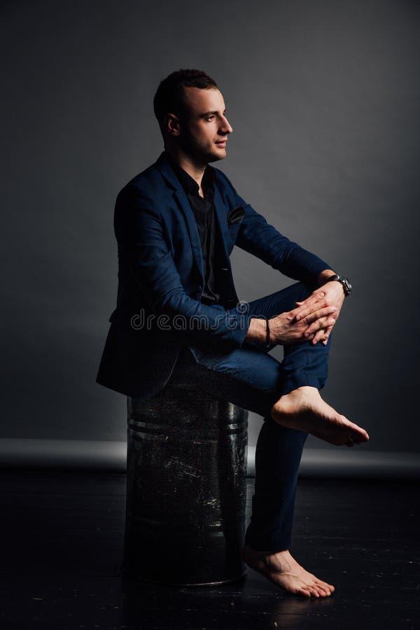 Το όμορφο μοντέρνο άτομο πορτρέτου σε ένα μαύρο πουκάμισο κάθεται σε μια καρέκλα σε μια σοφίτα στούντιο φωτογραφιών στοκ φωτογραφία