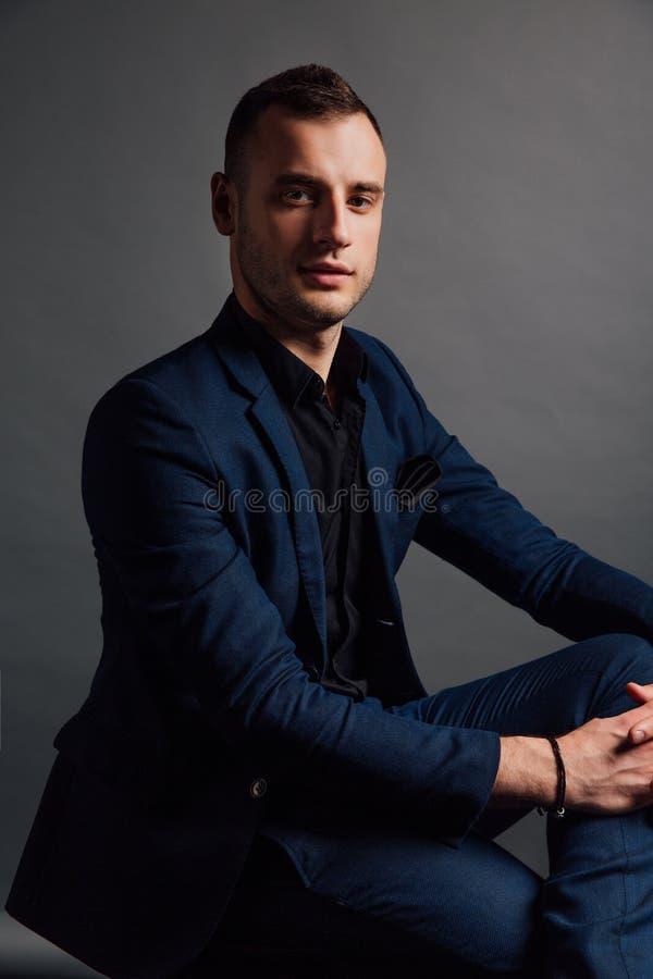 Το όμορφο μοντέρνο άτομο πορτρέτου σε ένα μαύρο πουκάμισο κάθεται σε μια καρέκλα σε μια σοφίτα στούντιο φωτογραφιών στοκ φωτογραφίες με δικαίωμα ελεύθερης χρήσης