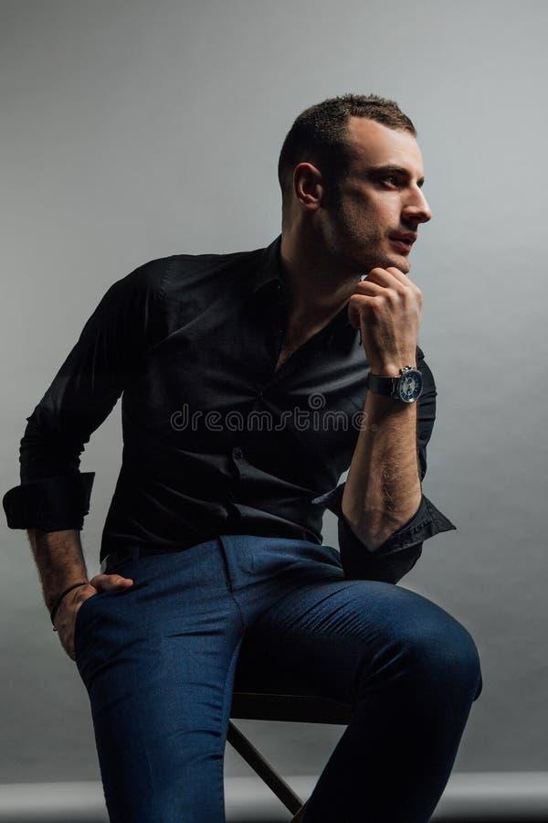 Το όμορφο μοντέρνο άτομο πορτρέτου σε ένα μαύρο πουκάμισο κάθεται σε μια καρέκλα σε μια σοφίτα στούντιο φωτογραφιών στοκ εικόνες