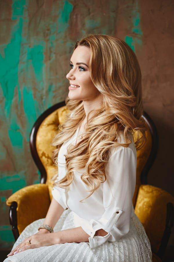 Το όμορφο μοντέρνο ξανθό πρότυπο κορίτσι με τα μπλε μάτια κάθεται στην εκλεκτής ποιότητας πολυθρόνα, στο εσωτερικό στοκ εικόνα