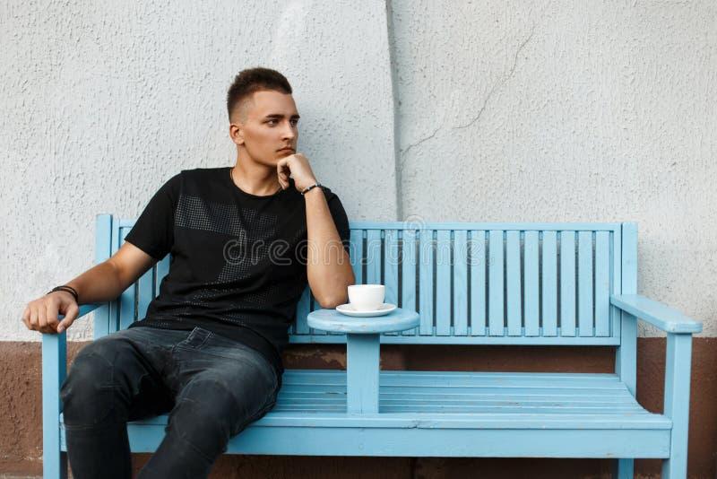 Το όμορφο μόνο άτομο κάθεται μόνο σε έναν πάγκο και πίνει τον καφέ στοκ εικόνες