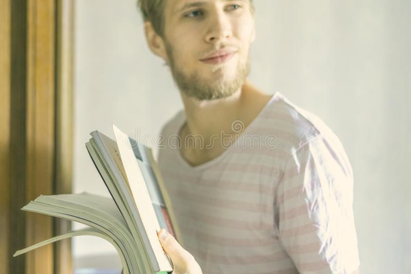 Το όμορφο νέο γενειοφόρο άτομο φέρνει το μικρό σωρό των βιβλίων στο πανεπιστημιακό φ στοκ φωτογραφίες με δικαίωμα ελεύθερης χρήσης