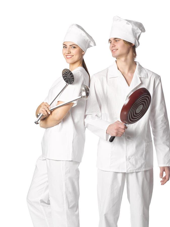 Το όμορφο νέο ζεύγος έντυσε στους μάγειρες με το μαγείρεμα της στάσης εργαλείων στοκ φωτογραφία