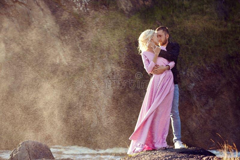 Το όμορφο νέο ζεύγος αγκαλιάζει και εξετάζει μακριά και το ένα το άλλο που απολαμβάνει μια ρομαντική ημερομηνία στον ποταμό η φωτ στοκ φωτογραφία