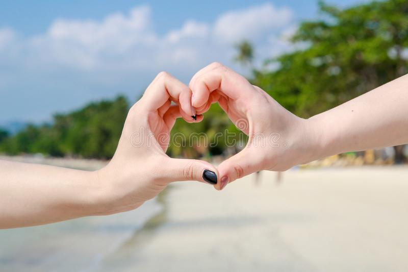 Το όμορφο νέο ζεύγος κάνει την καρδιά με τα δάχτυλα στοκ εικόνες