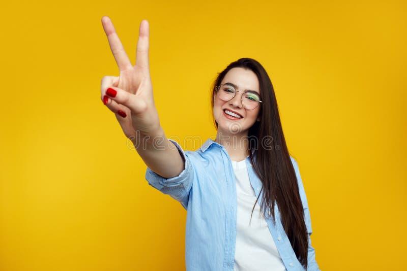 Το όμορφο νέο θηλυκό με eyeglasses έντυσε στο μπλε πουκάμισο και παρουσίαση χειρονομίας ειρήνης που απομονώθηκε πέρα από το πορτο στοκ φωτογραφία με δικαίωμα ελεύθερης χρήσης