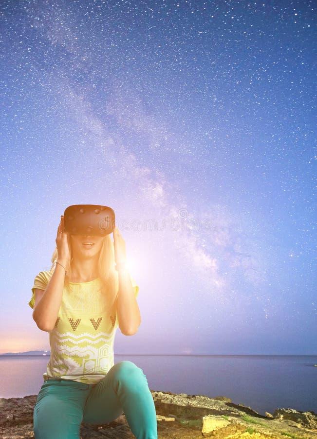 Το όμορφο νέο κορίτσι κοιτάζει στα γυαλιά της εικονικής πραγματικότητας, κοσμικά στοκ εικόνα